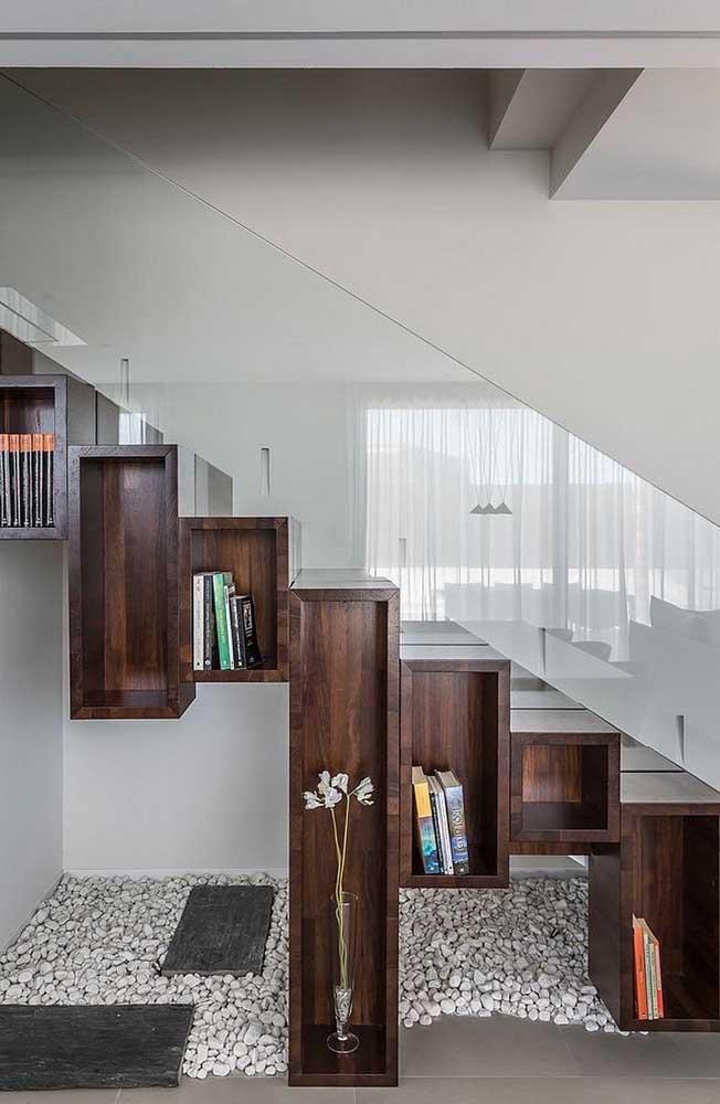 Jardim de pedras e nichos de madeira para decoração: o pequeno espaço embaixo dessa escada foi muito bem resolvido