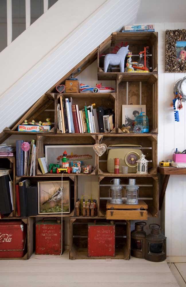 Embaixo dessa escada, os caixotes de madeira viram estante