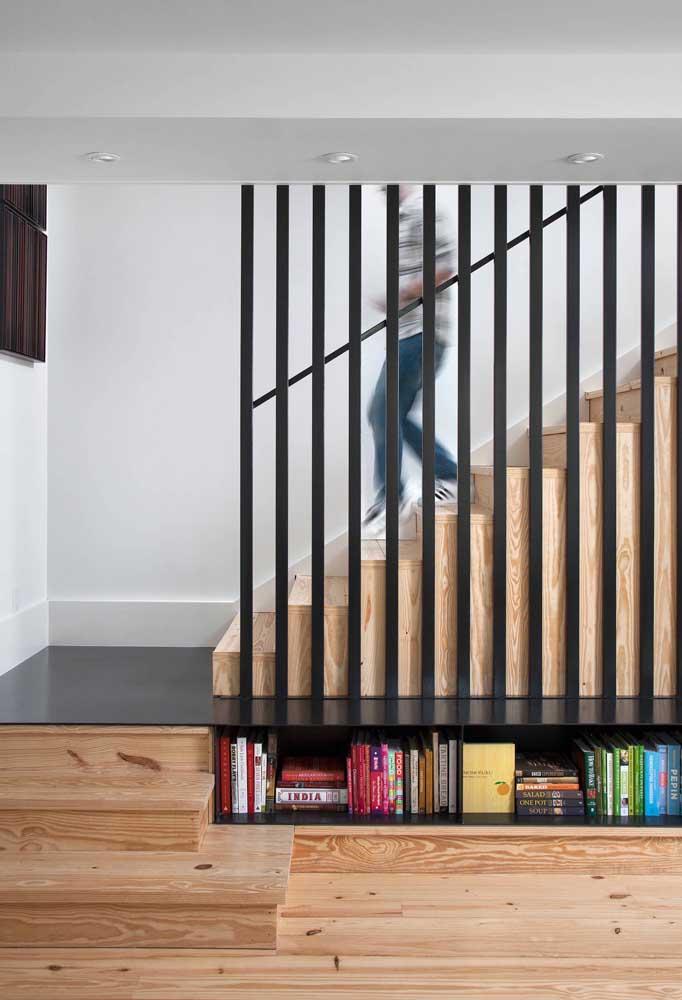 Aqui, o espaço embaixo da escada foi usado para criar um nicho aberto para os livros