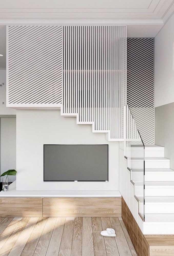 Essa escada com dois lances abriga junto a sua estrutura o painel para TV; uma ótima maneira de otimizar o espaço da sala de estar