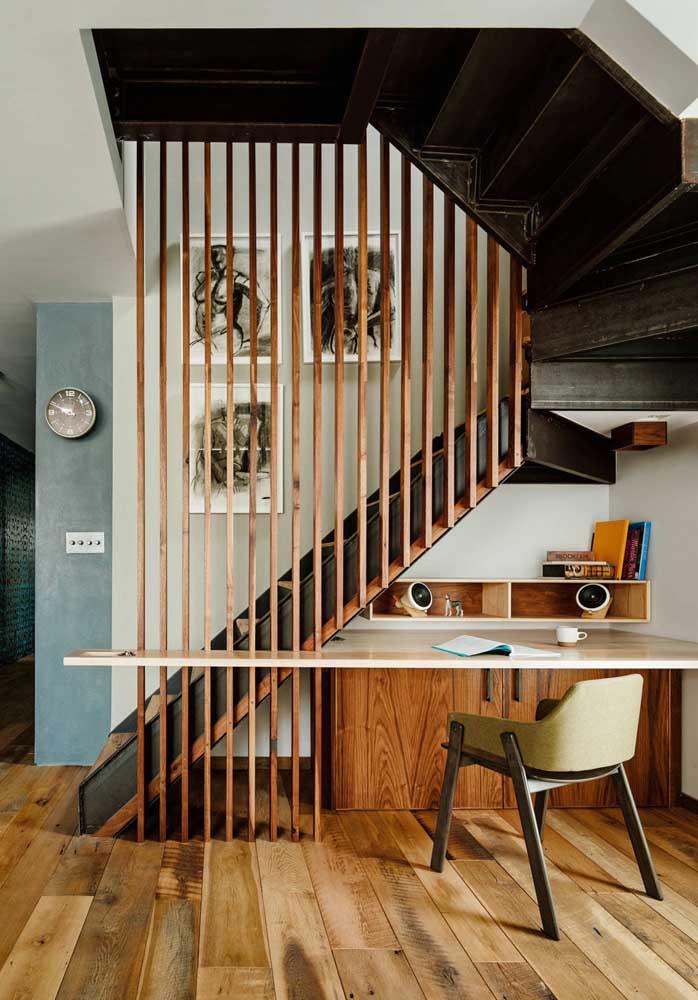 Um home office cheio de estilo preenche o pequeno espaço embaixo dessa escada de madeira