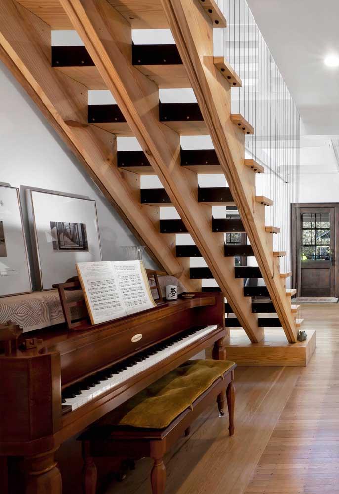 Linda inspiração de espaço embaixo da escada decorada; ideal para quem aprecia tocar algum instrumento musical