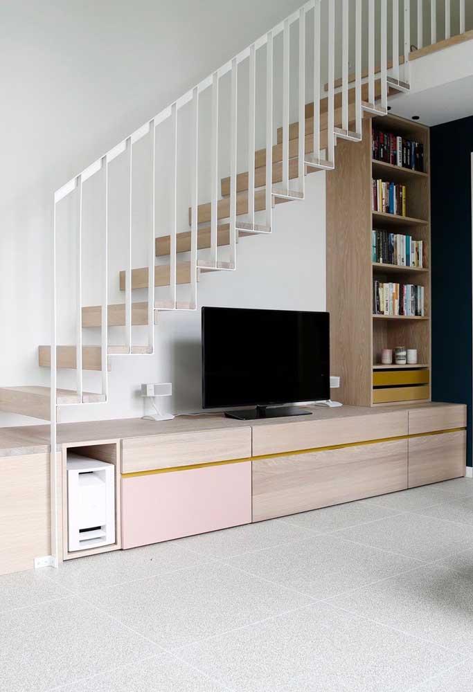 Rack, estante e TV ocupam o espaço embaixo dessa outra escada