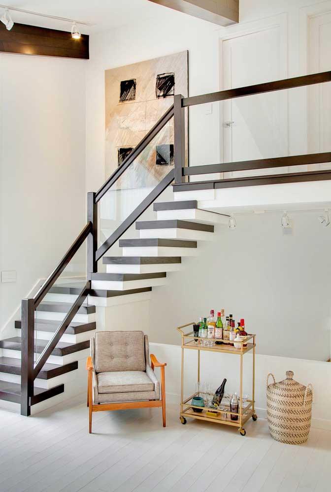 O amplo vão embaixo dessa escada serviu para abrigar o carrinho de bebidas e a poltrona