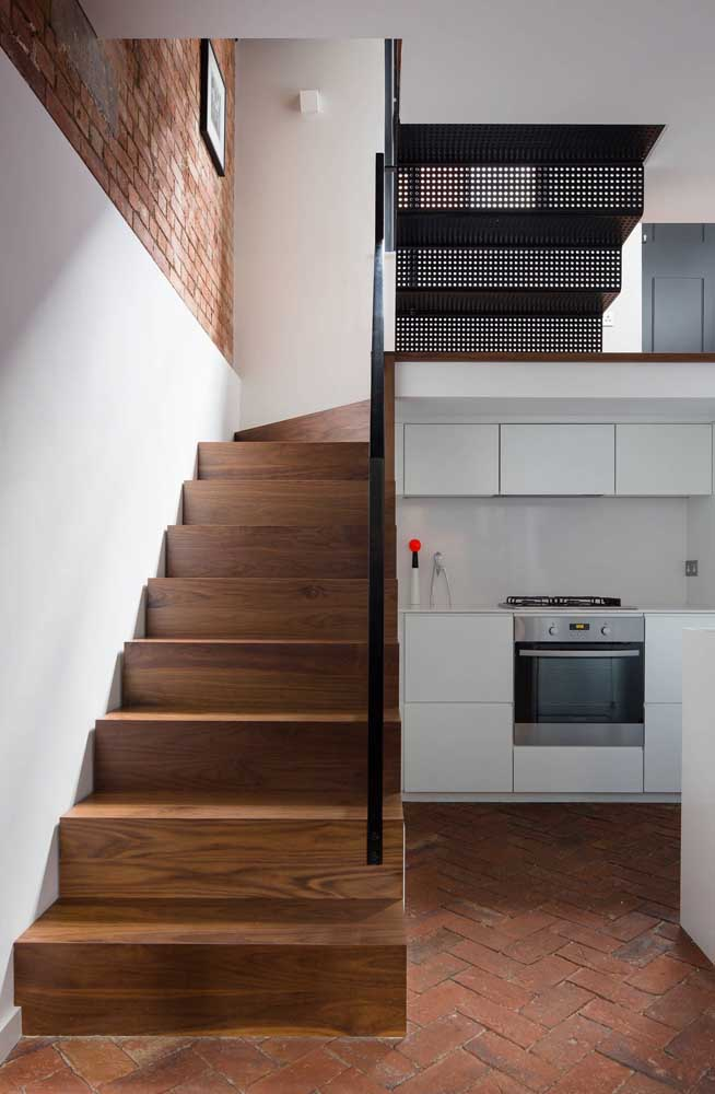 Casas pequenas precisam de soluções inteligentes; aqui, a proposta foi montar a cozinha embaixo da escada
