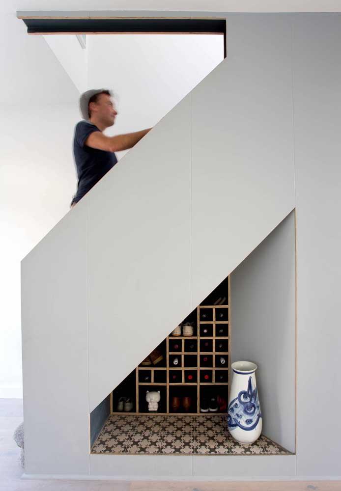 Embaixo dessa escada tem um pouco de tudo: garrafas, sapatos e objetos decorativos