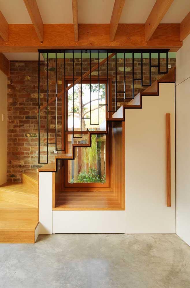 Ideia bonita e criativa para o espaço embaixo da escada; repare que a janela acompanha a extensão da parede, servindo ambos os espaços