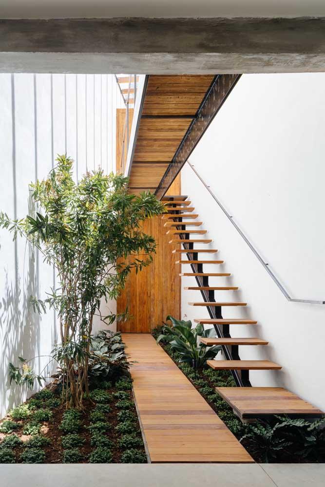 Essa linda escada de madeira com degraus vazados conta com a beleza de um pequeno canteiro abaixo dela