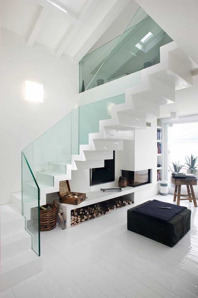 Já aqui, o espaço embaixo da escada foi aproveitado para criar um cantinho de relaxamento, com destaque para a lareira embutida na parede