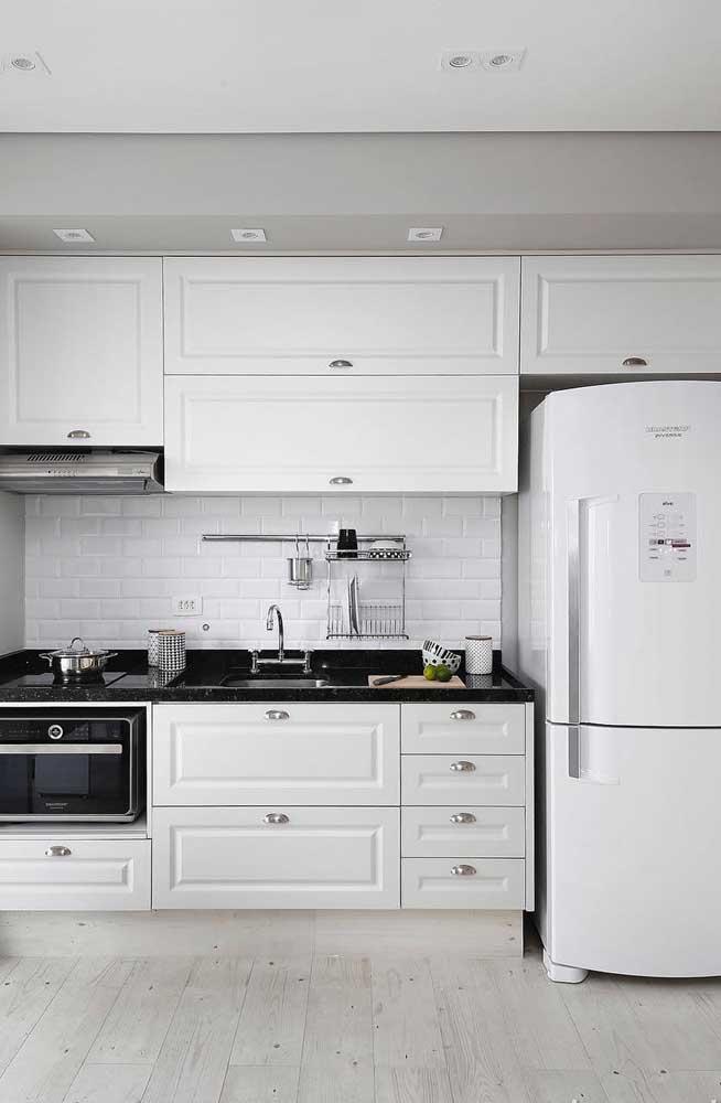 Cozinha branca, preta e cinza; destaque para o piso de madeira clara combinando com a paleta de cores do ambiente