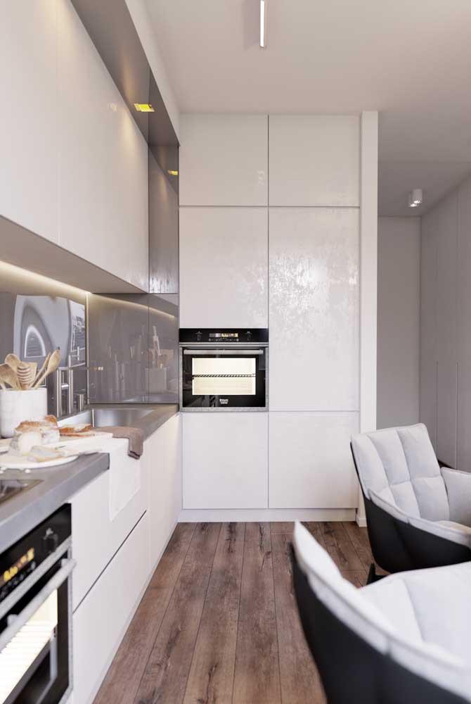 Cozinha branca com piso de madeira escura; opção elegante e neutra para o ambiente