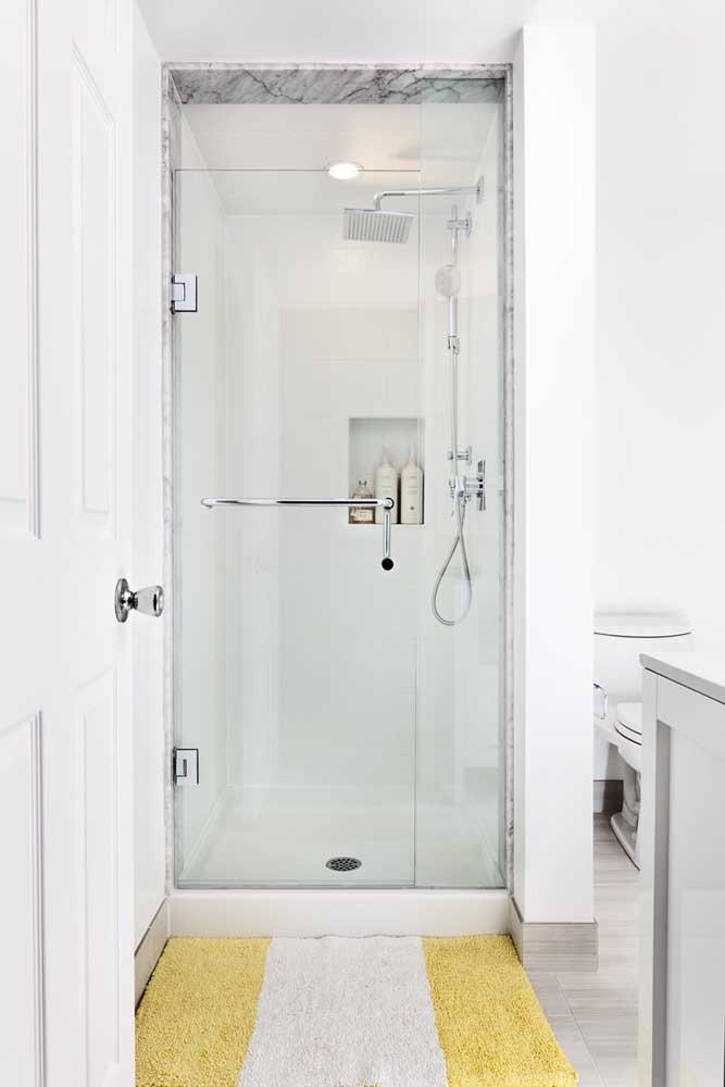 Nesse banheiro branco, o toque de cor fica por conta do tapete amarelo