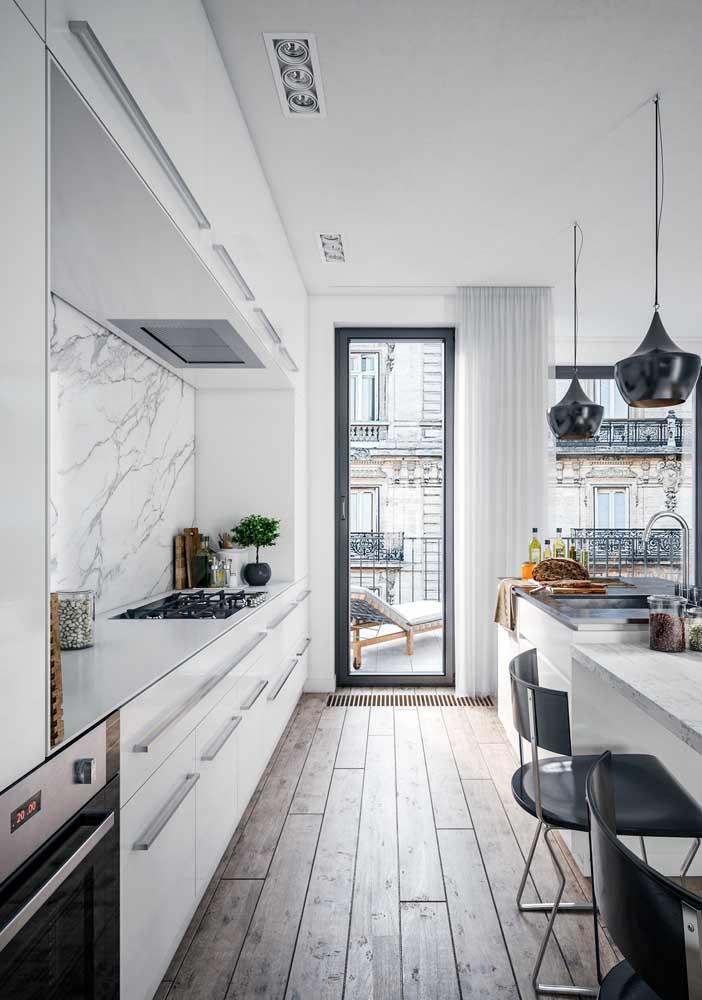 Nessa cozinha estreita, o branco contribui com a sensação de amplitude do ambiente; para quebrar a monotonia, algumas pinceladas de preto