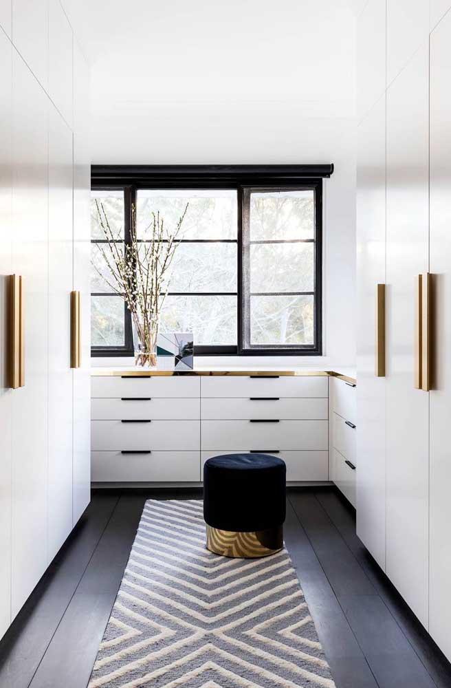A cor base desse closet é o branco, já os pontos diferenciados do espaço foram criados com o preto e o dourado