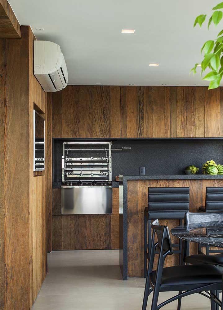Espaço gourmet com churrasqueira elétrica embutida; destaque para o contraste entre a madeira do revestimento e as peças de inox da churrasqueira