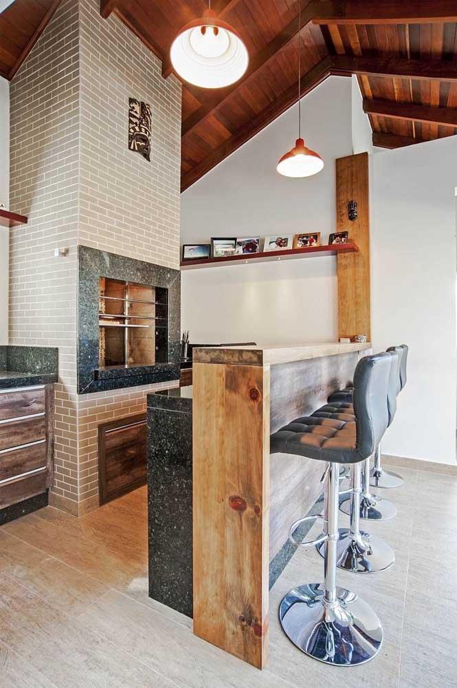 Espaço gourmet com churrasqueira elétrica embutida na parede de tijolinhos, remetendo às tradicionais churrasqueiras de alvenaria