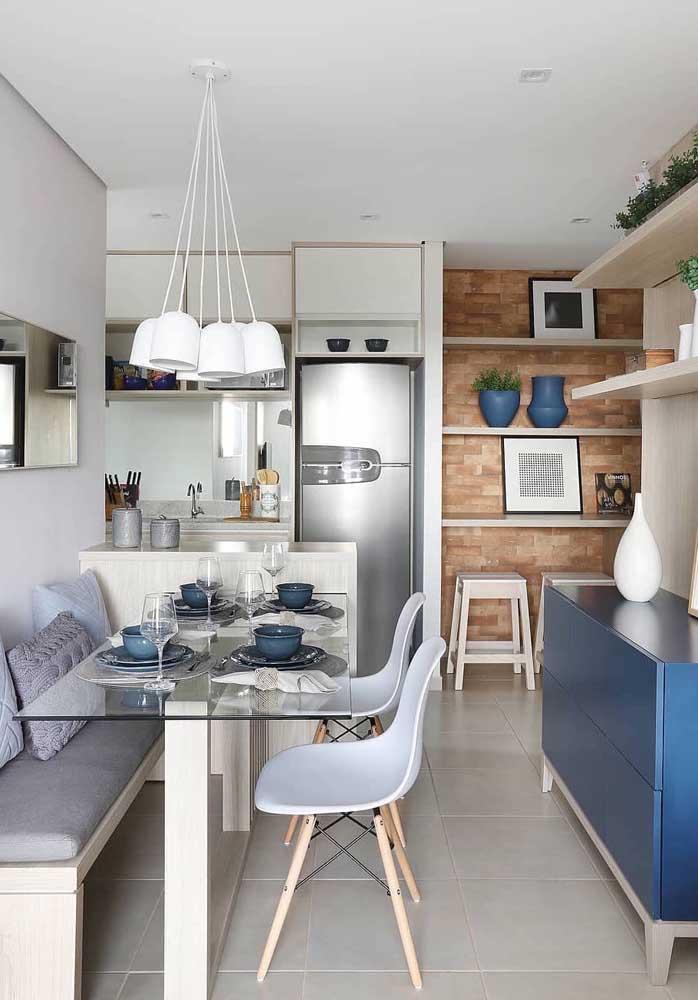 A solução para o espaço pequeno do apartamento é a cozinha integrada com a sala de jantar; destaque para o banco alemão