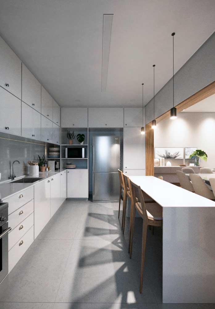 Cozinha ampla integrada pelo balcão à sala de jantar