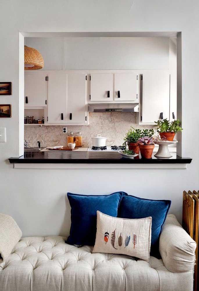 Esse modelo de cozinha ganhou uma abertura na parede para integrá-la à sala de estar
