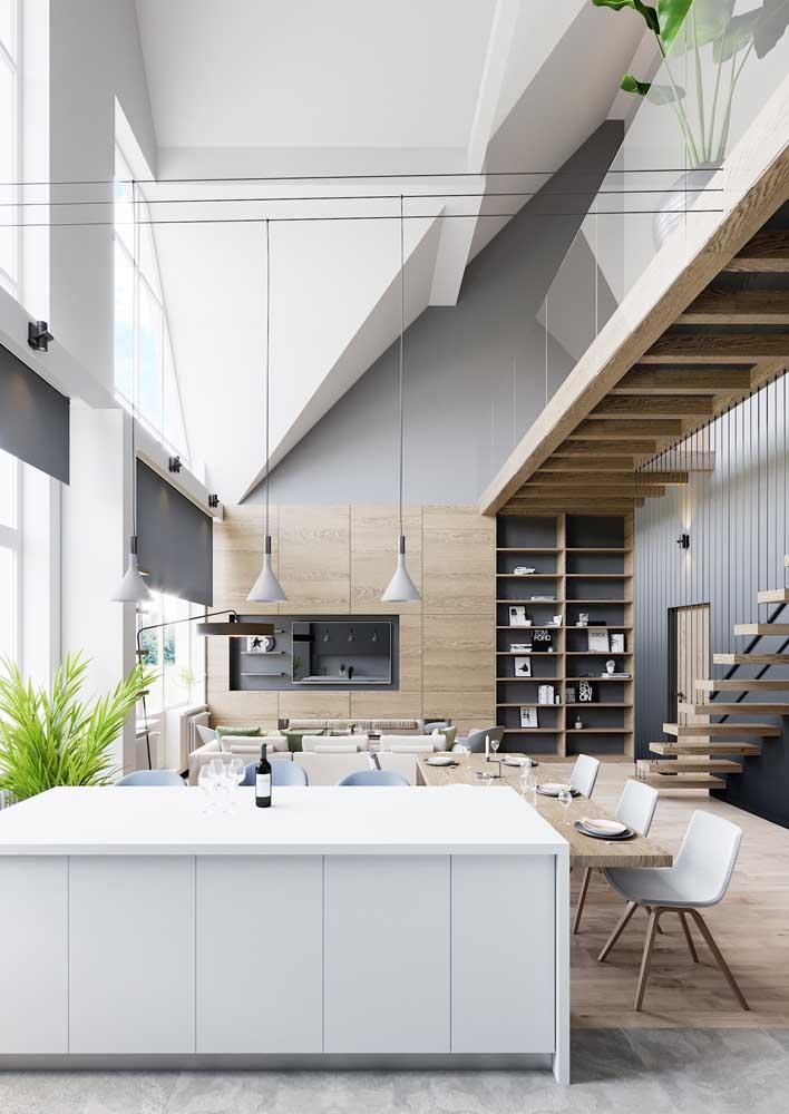 Cozinha integrada com sala de jantar e de estar; o ambiente com pé direito duplo garantiu a sensação de amplitude do espaço