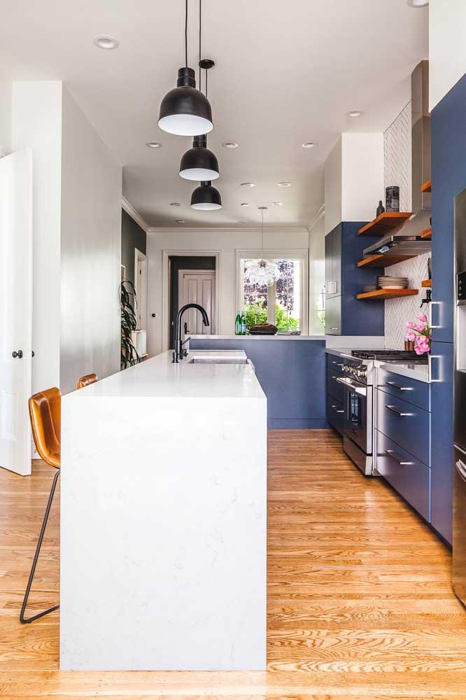 A ilha no centro da cozinha integrada ajuda a delimitar visualmente os ambientes