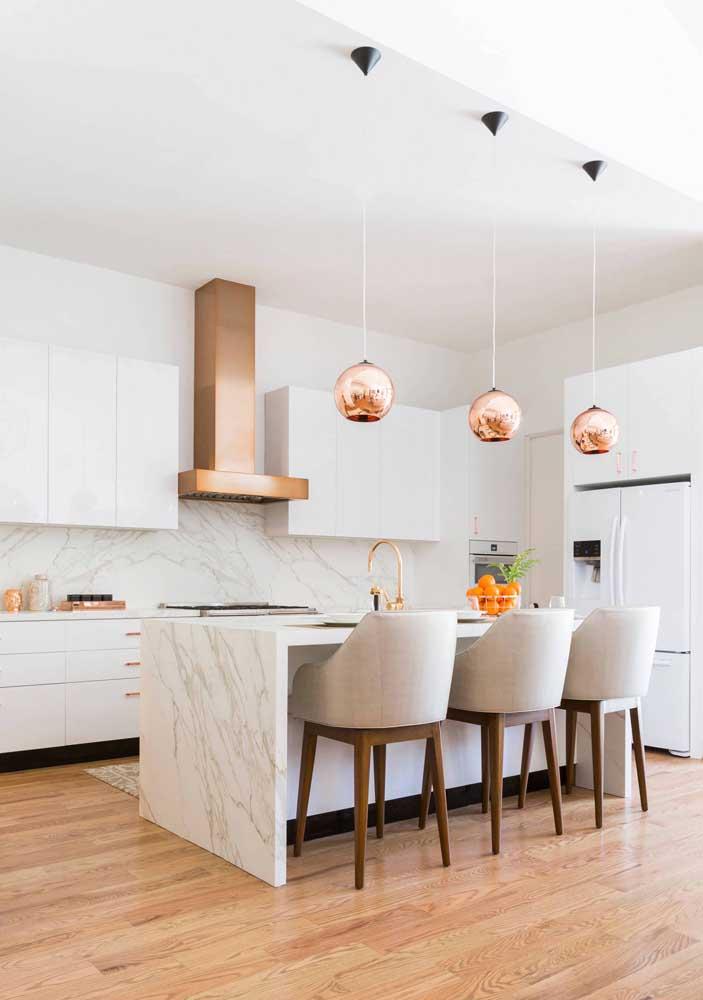 Cozinha integrada americana com balcão em mármore para combinar com o estilo elegante do ambiente; destaque para as luminárias rosé gold