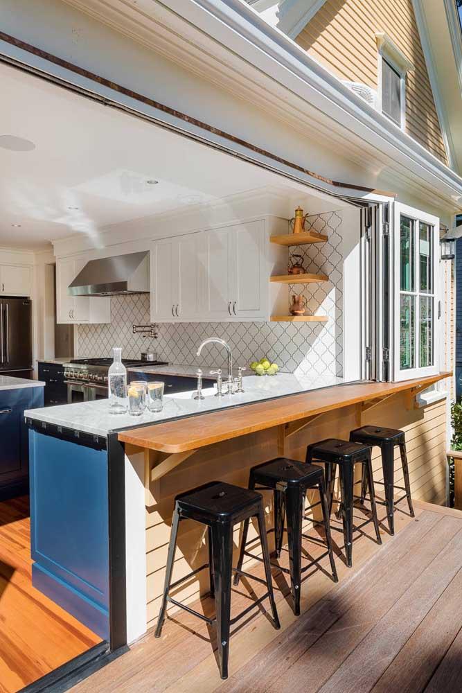 Cozinha integrada com a área externa da casa, um modelo perfeito para receber os familiares e amigos em um domingo ensolarado
