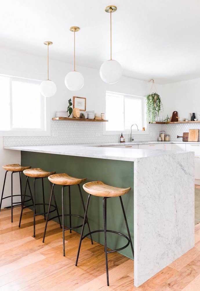 Cozinha integrada americana com bancada em mármore e detalhes clássicos nos pendentes