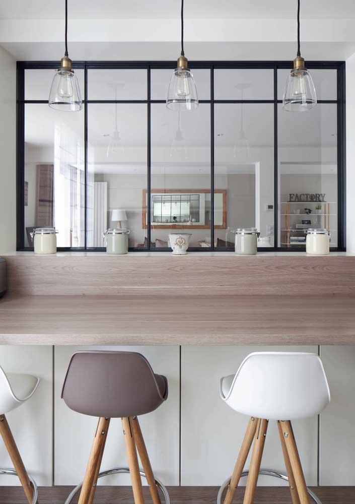A janela interna garante a visibilidade da cozinha integrada com a sala de estar da casa