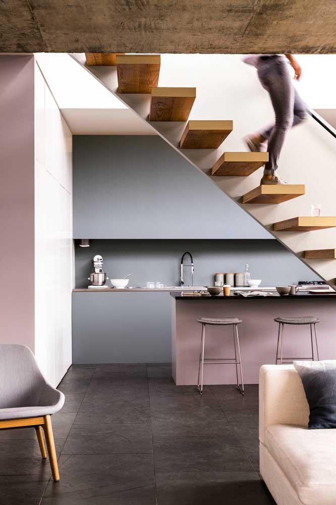 Cozinha integrada com armários sob medida contracenando com a escada logo à frente