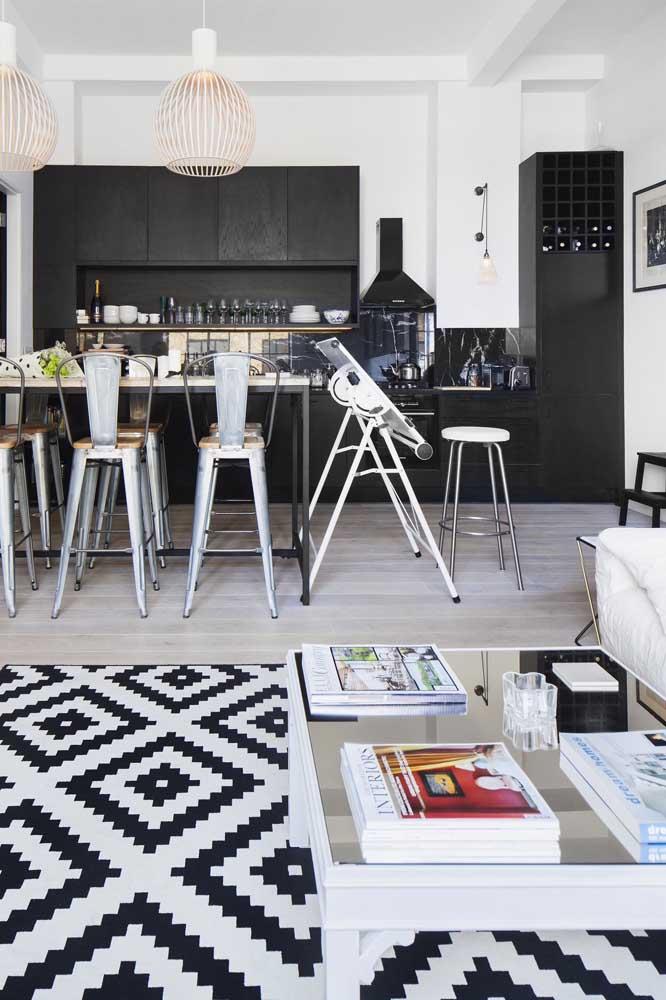 Cozinha integrada com sala de estar, em ambos os ambientes reina a paleta em preto e branco