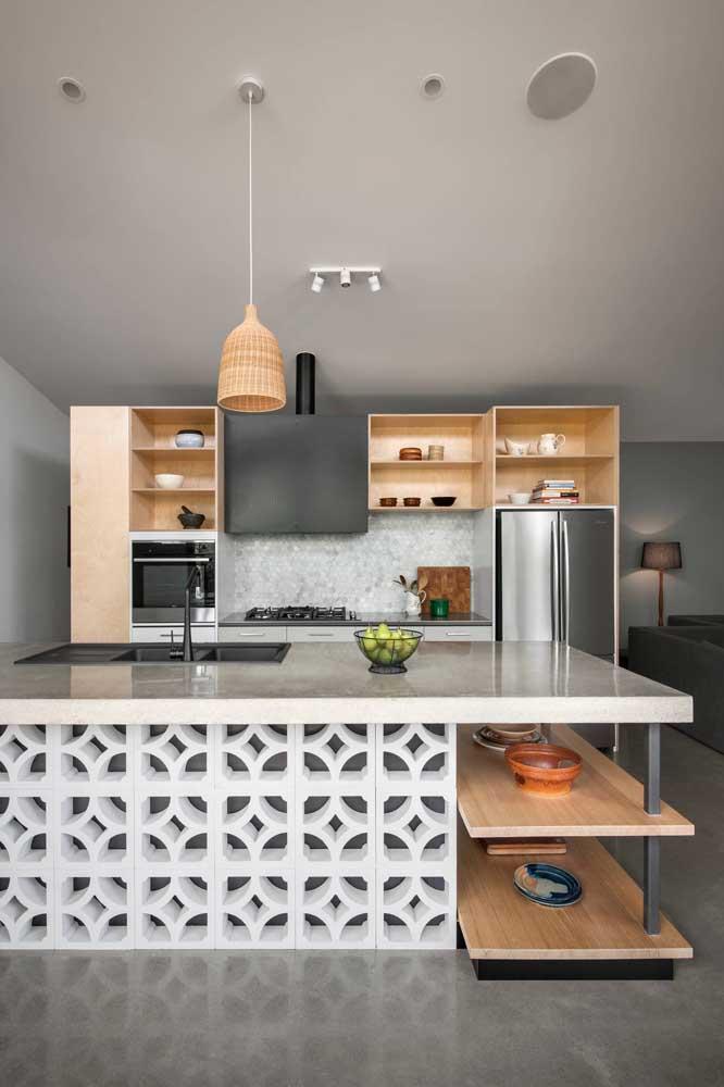 Cozinha integrada com ilha e móveis sob medida super funcionais; destaque para o uso charmoso dos cobogós sob a ilha
