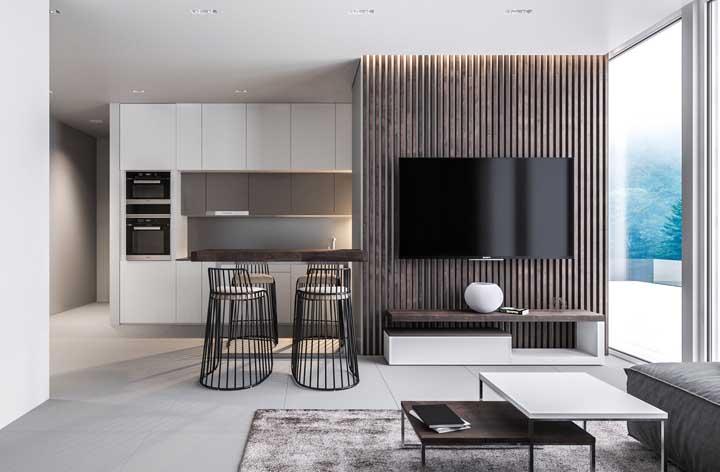 Cozinha moderna integrada com sala de estar; perceba a similaridade de tons e texturas nos dois ambientes