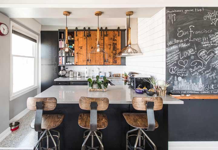 Cozinha integrada super descolada com banquetas em madeira e tinta lousa na parede