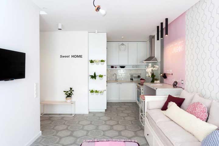 Tons claros e neutros deram vida a essa cozinha integrada com sala de estar; destaque para os detalhes da parede que ajudam a delimitar os ambientes