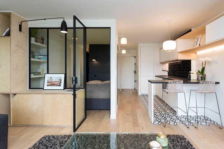 Cozinha integrada e demarcada pelo revestimento diferenciado que cobre o chão