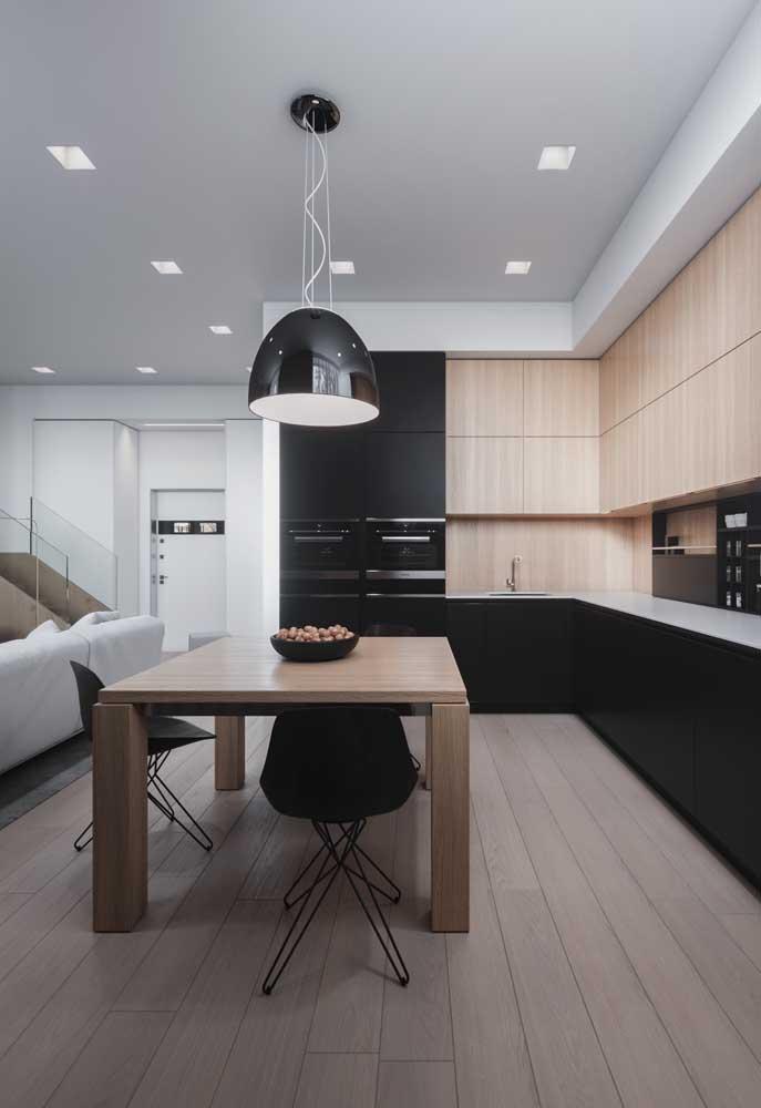 Cozinha integrada com sala de jantar e sala de estar com móveis sob medida em madeira; destaque para o pendente escolhido para o ambiente