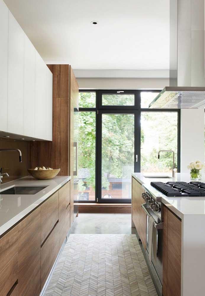 A cozinha integrada com a varanda garantiu uma vista linda para a área verde da casa