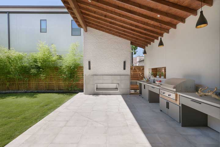 Nesse espaço gourmet no quintal a escolha foi por um piso cinza de cerâmica que combina com as paredes e armários do espaço
