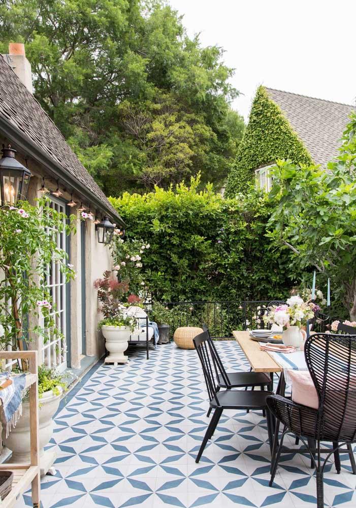 A casa de estilo rústico trouxe um piso para quintal de desenho marcante em tons de azul e branco, tornando-se o destaque do ambiente