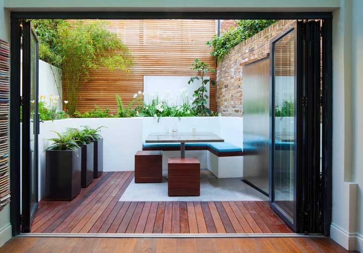 Pequeno quintal integrado à área interna; em ambos os ambientes se destaca o piso de madeira