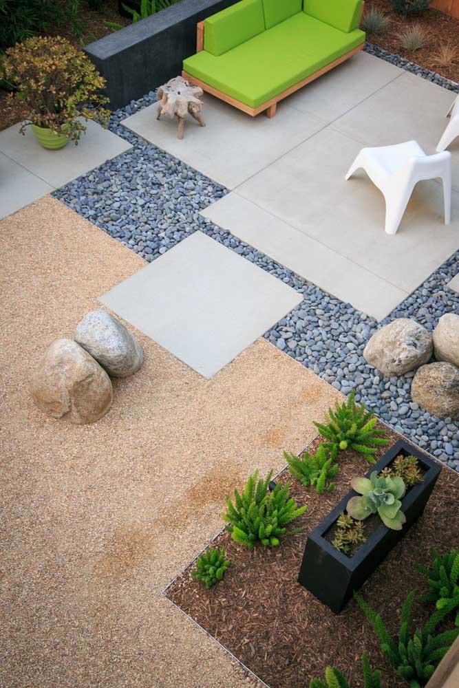 Dois tipos de pedras diferentes foram usadas para cobrir a superfície desse quintal; entre elas, o piso de concreto