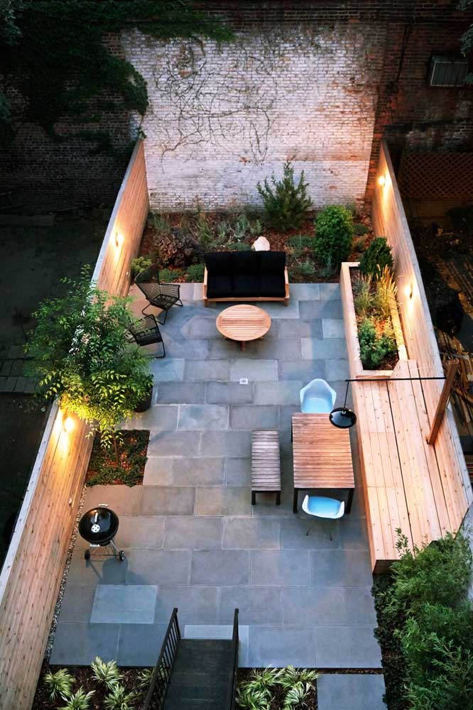 Nesse quintal acolhedor, a opção foi por um piso de cerâmica cinza, muito similar à ardósia