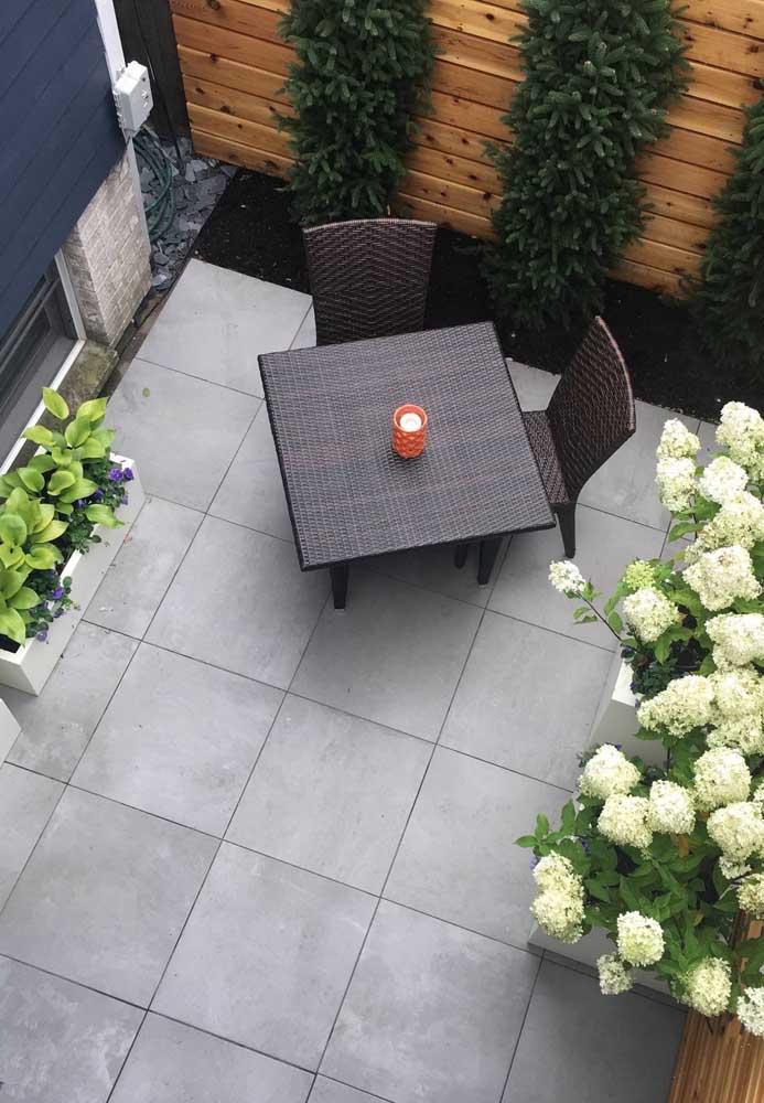 Mais uma inspiração de piso cinza para quintal; aqui, ele se combina aos tons de madeira e ao verde das plantas
