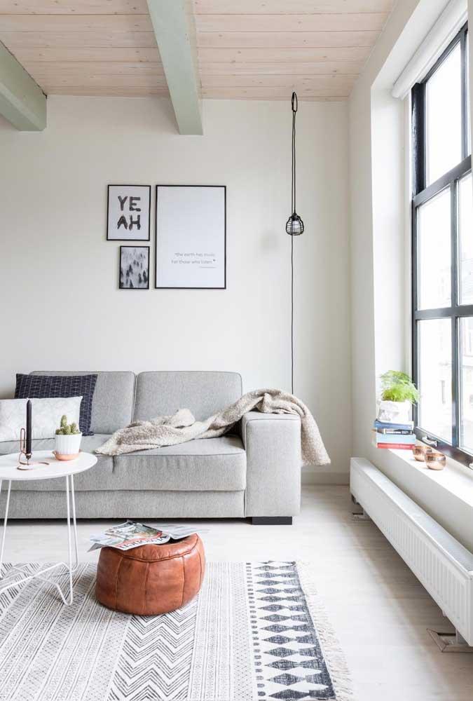 Nessa sala de estar em tons neutros, o puff redondo de couro chama toda atenção para si, mesmo sendo pequeno
