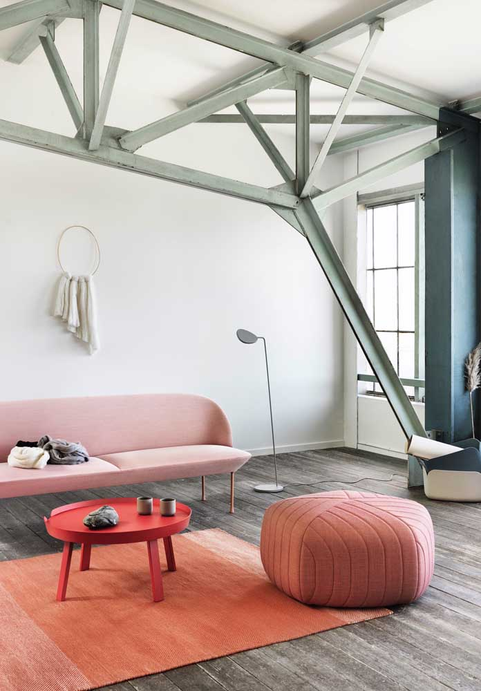 Sala de estar grande com puff redondo cor de rosa; proporção ideal para o tamanho do ambiente