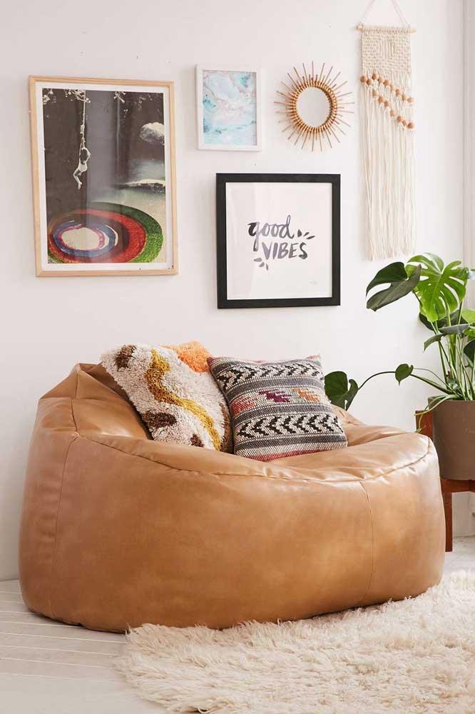 A sala de estar boho apostou em um puff redondo gigante em couro que pode, tranquilamente, substituir o sofá