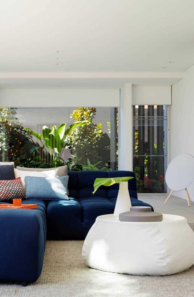 Já nessa sala de estar, o puff branco forma um lindo contraste com o sofá azul royal