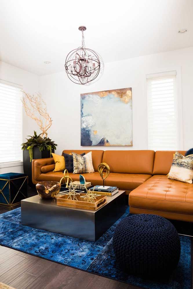 Essa sala de paleta azul e marrom contou com o puff redondo de crochê azul marinho para completar o número de assentos do sofá