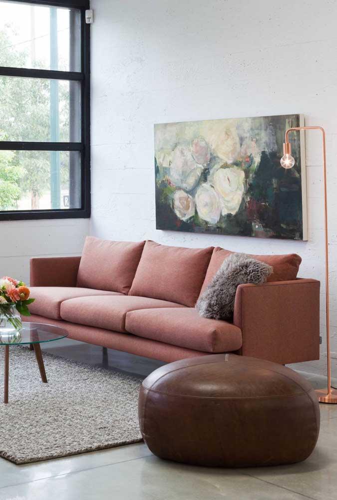 Sala de decoração neutra e romântica com puff redondo de couro marrom